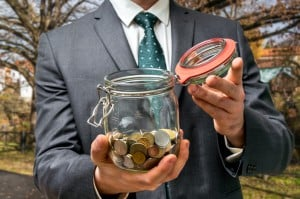 Businessman in black suit holding money jar with coins